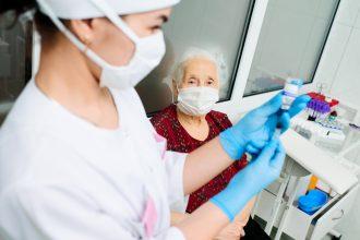 nurse giving vaccine to elderly patient